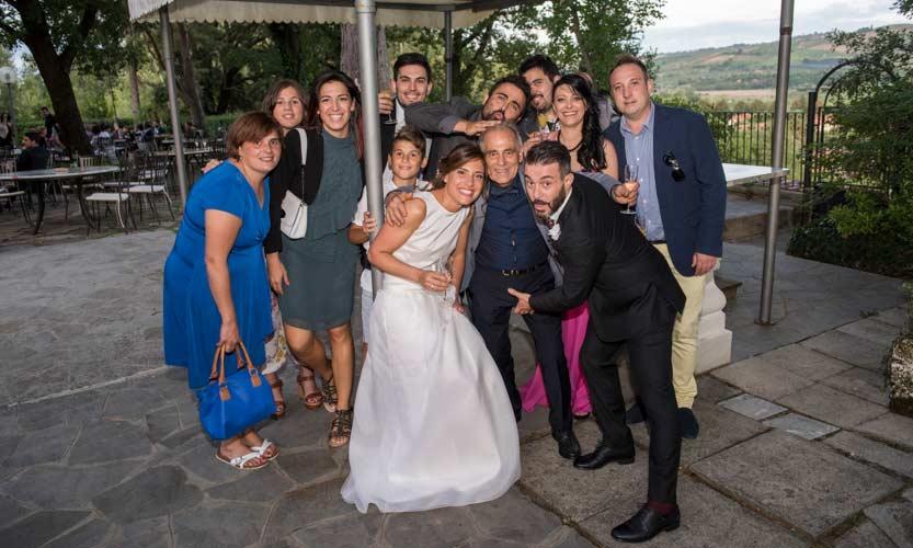 Scatto di un fotoreporter matrimonio che ritrae un gruppo di inviati scherzoso con al centro gli sposi che li circondano