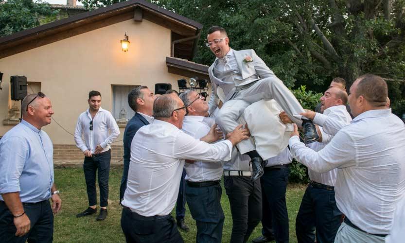 Fotogramma di un videomaker matrimonio che riprende lo sposo che seduto su di una sedia viene sollevato in aria da un gruppo di spericolati invitati