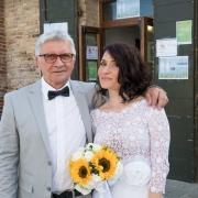 Fotografo-matrimonialista con sposa e il babbo che la tiene vicina con il braccio. Le mani della sposa tengono un bouquet di girasoli