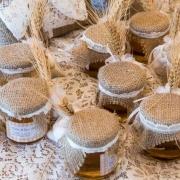 Servizio-fotografico-le-bomboniere-degli-sposi vasetti contenenti miele adornati con panno marrone e spiga di grano