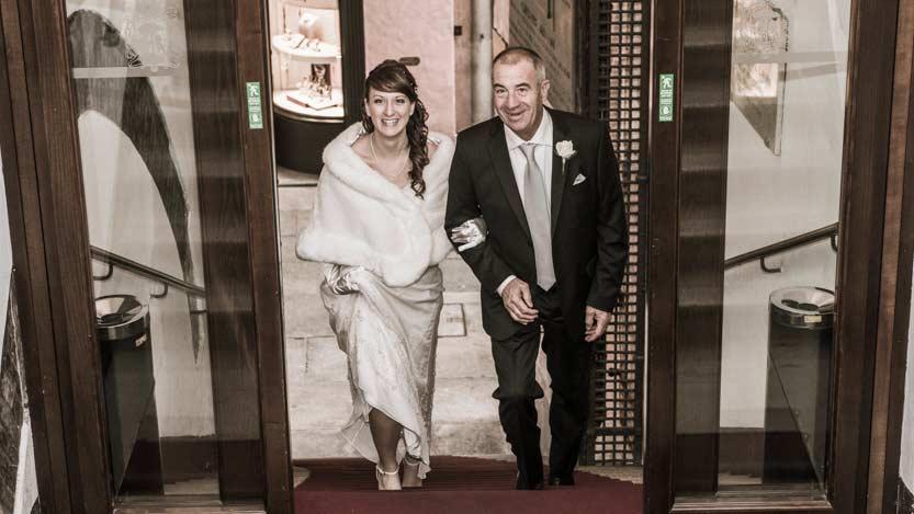 Servizio fotografico matrimonio: la sposa sale le scale del municipio di Ravenna a braccetto del suo babbo molto emozionato.