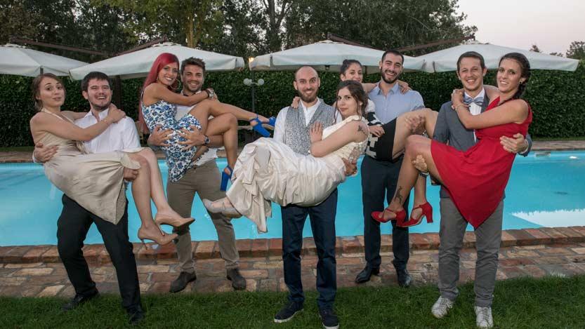 Fotografo matrimonio con la sposa ed alcune amiche prese in braccio dai reciproci parte a bordo piscina