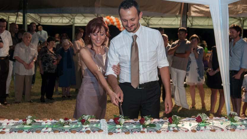 Fotografo matrimonio di Katia e Ivan mentre stanno tagliando la torta nuziale sotto un gazebo
