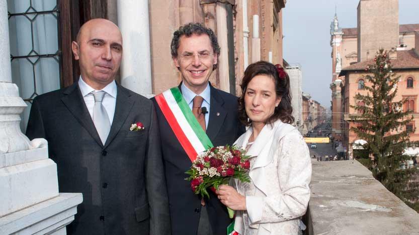 Fotografo matrimonio Bologna con gli sposi e l'assessore affacciati al balcone del municipio