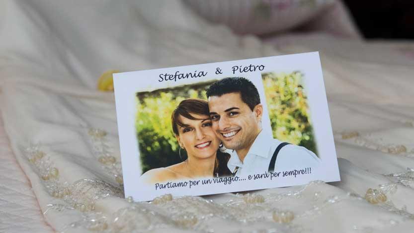 Partecipazione matrimonio cartacea sopra un abito da sposa