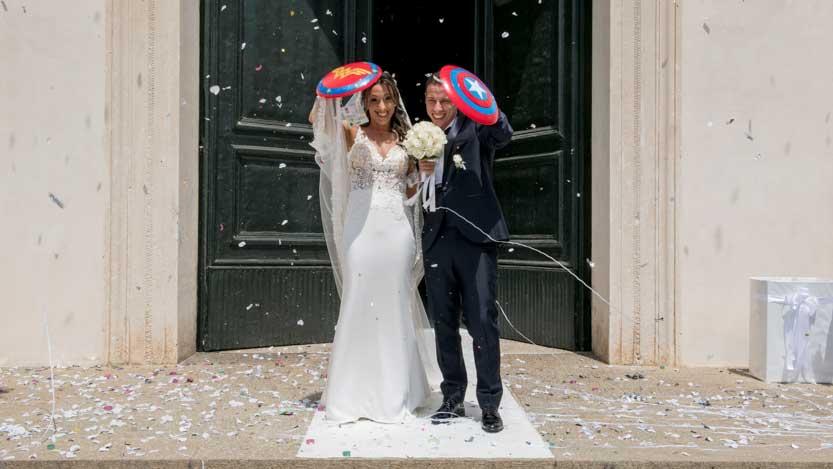 Immagini divertenti matrimonio sposi all'uscita della chiesa con gli scudi