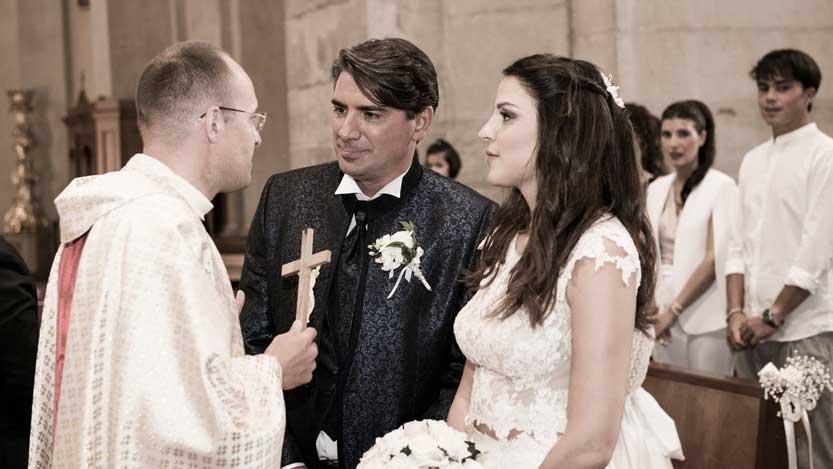 Foto di matrimonio il Sacerdote mostra il Crocifisso algli sposi