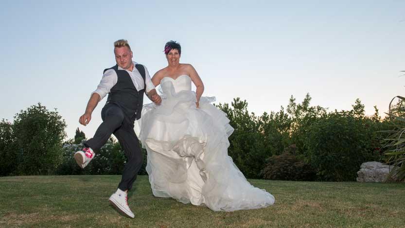 Foto di matrimonio sposi che saltano in mezzo al prato