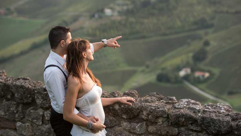 Foto sposi al tramonto osservano abbracciati il paesaggio